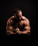 Heißer muskulöser Mann auf einem schwarzen Hintergrund Ein hemdloser Bodybuilder, der Trizeps und Bizeps vorführt Hartes Training stockbild