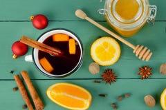 Heißer roter Glühwein auf hölzernem Hintergrund mit orange Scheibe, Anis Stockfotografie
