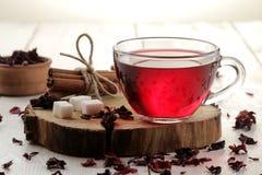 Heißer roter karkade Tee in den Glasschalen mit trockenem Tee auf einem weißen Holztisch lizenzfreies stockfoto