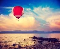 Heißer roter Luft-Ballon, der über Meer bei Sonnenuntergang fliegt Stockfotos