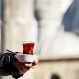 Heißer türkischer Tee draußen mit einer Moschee am Hintergrund Turkis Lizenzfreies Stockbild