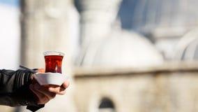 Heißer türkischer Tee draußen mit einer Moschee am Hintergrund Turkis Stockfoto