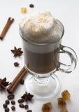 Heißer Tasse Kaffee mit gepeitschtem Milchschaum auf dem weißen Hintergrund mit Zimtstangen, Sterne des Anises und lizenzfreie stockfotos