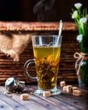 Heißer Tee in einem transparenten Becher auf hölzernem Hintergrund Lizenzfreie Stockfotografie