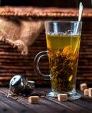 Heißer Tee in einem transparenten Becher auf hölzernem Hintergrund Stockfoto