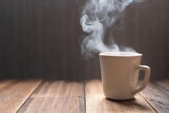 Heißer Tee/Kaffee in einem Becher auf einem Holztischhintergrund stockfoto