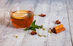 Heißer Tee mit Gewürzen auf einem Holztisch Stockbild