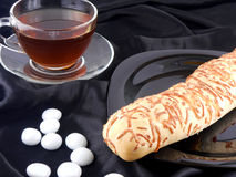 Heißer Tee mit Käsebrot und weiße Steine auf schwarzem Hintergrund Lizenzfreies Stockfoto
