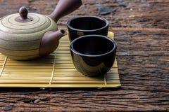 Heißer Teetopf auf Bambusmatte mit Schale auf Holztisch Stockbilder