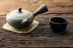 Heißer Teetopf auf Bambusmatte mit Schale auf Holztisch Lizenzfreies Stockbild