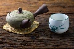 Heißer Teetopf auf Bambusmatte mit Schale auf Holztisch Lizenzfreie Stockfotos