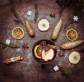 Heißer Weindurchschlag in der dunklen Schale mit Wintergewürzen und -früchten auf Holztisch Lizenzfreies Stockfoto