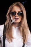 Heißes blondes Modell, das auf schwarzem Hintergrund raucht Stockfotos