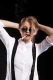 Heißes blondes Modell, das auf schwarzem Hintergrund raucht Lizenzfreies Stockbild