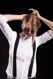 Heißes blondes Modell, das auf schwarzem Hintergrund raucht Lizenzfreie Stockfotografie