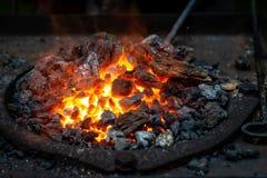 Heißes Einzelteil wird in die Schmiedeschmiede eingefügt, von der die Zungen der Flamme Konzept: Blacksmithing, Schmiede stockfoto