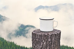 Heißes Getränk draußen auf dem Hintergrund der nebelhaften Berge Lizenzfreie Stockfotografie