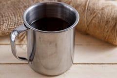 Heißes Getränk in einem Weinlesebecher auf einem hölzernen Hintergrund Spitzen- und Seitenansicht lizenzfreies stockfoto