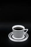 Heißes Getränk in gestreifter Schale auf dem schwarzen Hintergrund Stockfotos