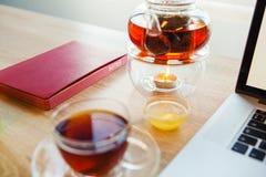 Heißes Getränk mit Arbeitszubehör stehen auf Tabelle stockbild