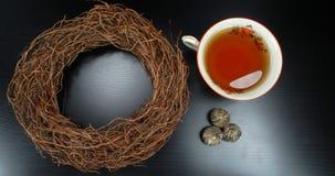 Heißes Teeschale weißes porselain mit Teeblumen mit Weidenkranzdekorationsring am hölzernen Hintergrund gerade für eine Einladung stockfotos