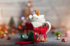 Heißes Wintergetränk in einem Becher mit warmem Schal Stockfotografie