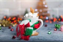 Heißes Wintergetränk in einem Becher mit warmem Schal Lizenzfreie Stockfotos