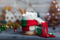 Heißes Wintergetränk in einem Becher mit warmem Schal Stockbild