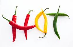 Heißes Wort gemacht vom roten, gelben und grünen Pfeffer des scharfen Paprikas auf whi Lizenzfreies Stockfoto