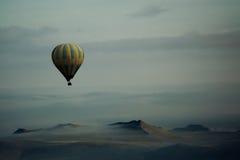 Heißluft-Ballon über Bergen stockbilder