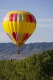 Heißluft-Ballon über Treed Hügel Stockbilder
