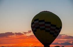 Heißluft-Ballon, der mit untergehender Sonne füllt Lizenzfreie Stockfotos