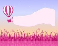 Heißluft-Ballon-Fliegen im Himmel mit Fahne Lizenzfreies Stockbild
