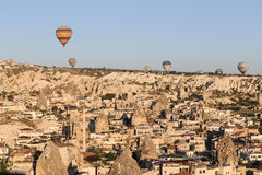 Heißluft-Ballone über Goreme-Stadt Lizenzfreie Stockfotografie