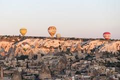 Heißluft-Ballone über Goreme-Stadt Lizenzfreie Stockfotos