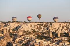 Heißluft-Ballone über Goreme-Stadt Stockbilder