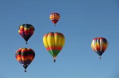 Heißluft-Ballone, die gegen einen blauen Himmel schwimmen Lizenzfreies Stockfoto