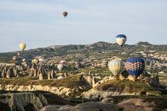 Heißluft Ballons über der alten Höhlen-Stadt in Cappadocia stockbild