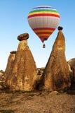 Heißluft baloon, das über großartige Steinklippen in Cappadocia fliegt stockfotografie