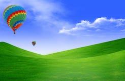 Heißluft baloon, das in den Himmel über Land schwimmt Stockbilder