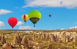Heißluft baloons, die über großartige Steinklippen in Cappadocia fliegen lizenzfreies stockfoto