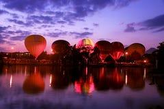 Heißluft baloons, die in den Abendhimmel nahe dem See fliegen Lizenzfreies Stockfoto