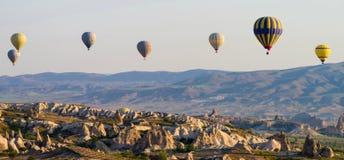 Heißluft steigt bei dem Sonnenaufgang im Ballon auf, der über Cappadocia, die Türkei fliegt stockfoto