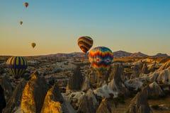 Heißluft steigt bei dem Sonnenaufgang im Ballon auf, der über Cappadocia, die Türkei fliegt Ein Ballon mit einer Flagge von der T stockfotografie