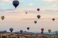Heißluft steigt bei dem Sonnenaufgang im Ballon auf, der über Cappadocia, Goreme, die Türkei fliegt lizenzfreies stockbild