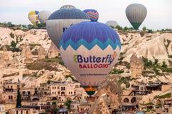 Heißluft steigt das Fliegen über Goreme bei Sonnenaufgang im Ballon auf stockfoto