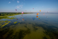 Heißluft steigt das Fliegen über See im Ballon auf Stockfoto
