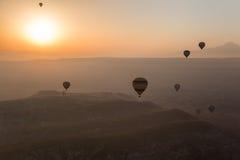 Heißluft steigt das Steigen über Cappadocia-Horizont am frühen Morgen im Ballon auf stockbilder