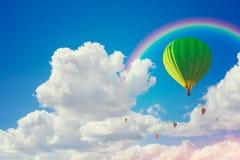 Heißluftballloons und -regenbogen mit bewölktem Hintergrund des blauen Himmels stockfoto