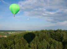 Heißluftballon über dem Feld mit blauem Himmel Lizenzfreie Stockfotografie